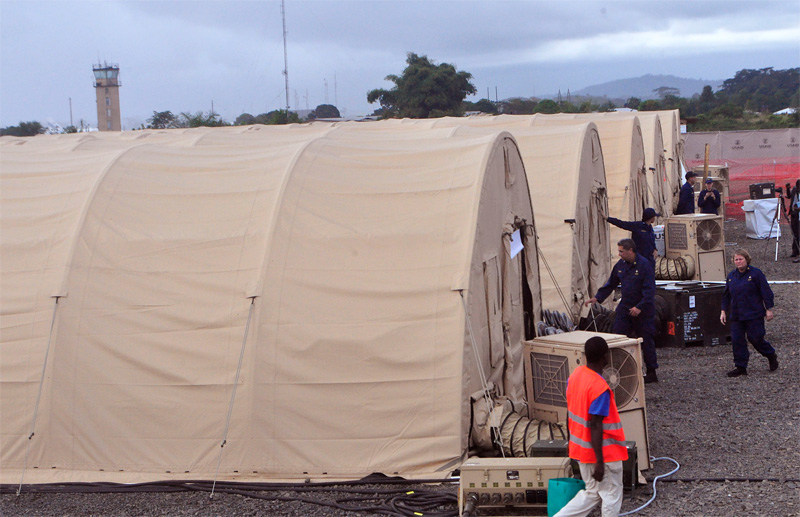 In this photo taken Wednesday Nov. 5, 2014, on the outskirts of the city of Monrovia, Liberia, health workers walk around medical tents that form part of a new American clinic to be used for the treatment of people suffering from the Ebola virus. As the Ebola epidemic flares in new hot spots and dims in others, the response to its shifts must catch up, experts say, and that's a challenge because it is a slow process for governments to authorize aid, to gather it together and then deliver it. And to build treatment units, even rudimentary ones, takes even more time. By the time it's built, the outbreak may have moved elsewhere. (AP Photo/Abbas Dulleh)
